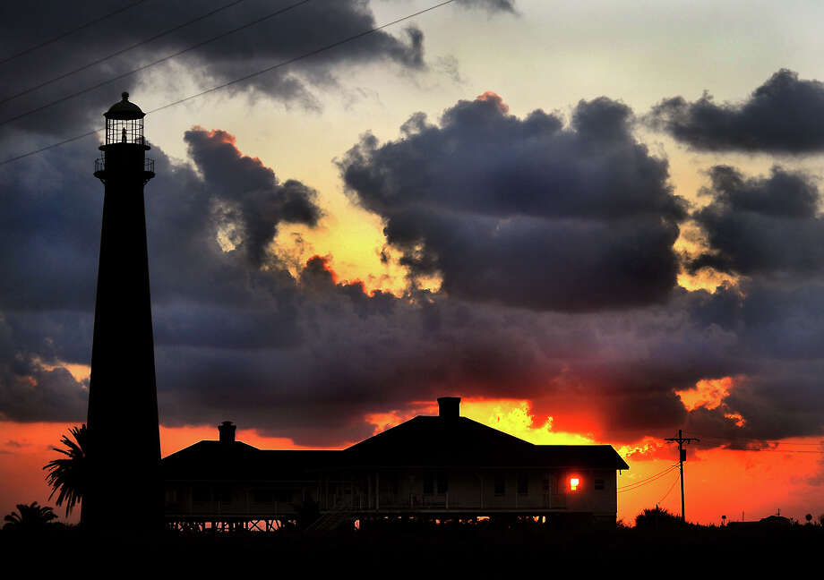 The sun sets behind the lighthouse on the Bolivar Peninsula.  Tammy McKinley/The Enterprise Photo: TAMMY MCKINLEY