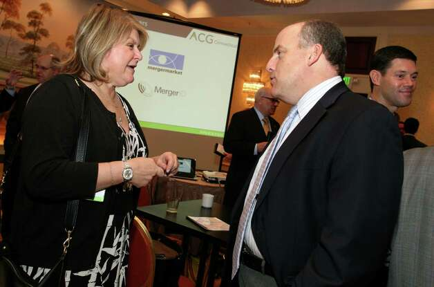 Angie DeGore talks with Paul Schuldiner during the Connecticut Association for Corporate Growth's 9th Annual Private Equity Exposition Friday, Dec. 7, 2012. Photo: DAVID AMES / GREENWICH TIME FREELANCE