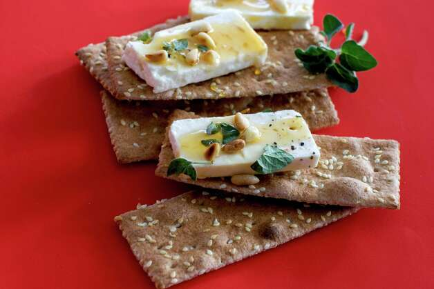 In this undated image, feta cheese and honey are shown served on crackers in Concord, N.H. (AP Photo/Matthew Mead) Photo: Matthew Mead, FRE / FR170582