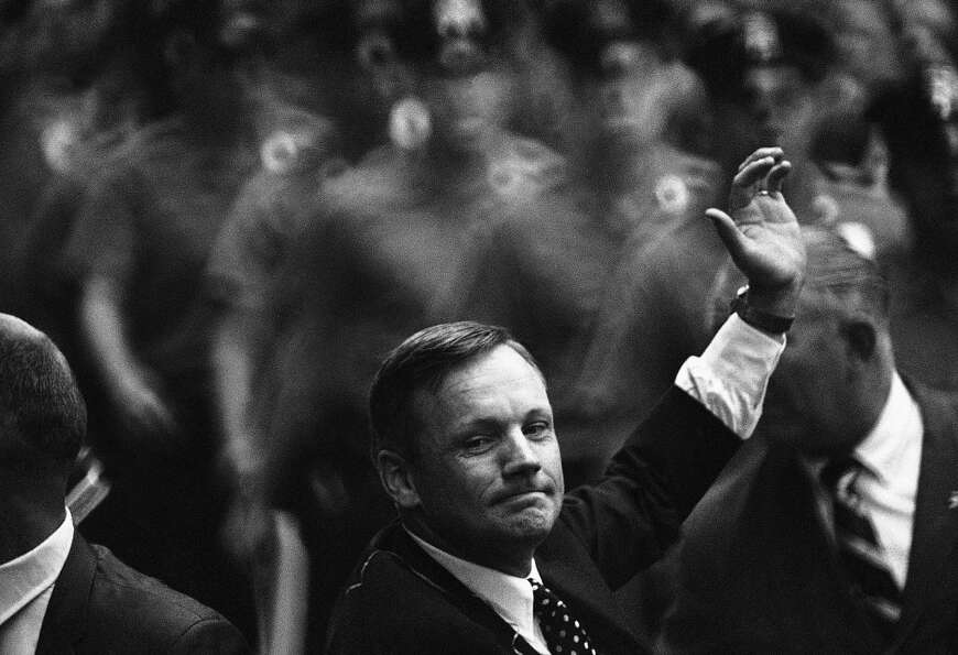 Astronauts Neil A. Armstrong, the first man on the moon, wave to the crowd during ticker tape parade