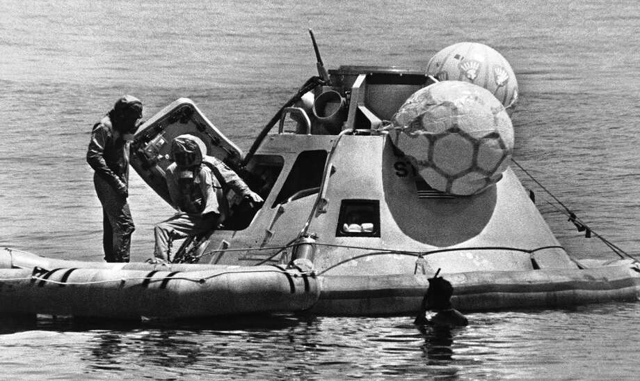 Neil Armstrong, flight commander of the Apollo 11 space flight, steps from a command module mockup during egress training in the Gulf of Mexico, July 8, 1969. Armstrong slated to be the first man to set foot upon the moon, wear a Biological Isolation garment, (BIG), which all Apollo 11 crew members will wear when returning to earth. Man at left is unidentified. (AP Photo/NASA) (ASSOCIATED PRESS)