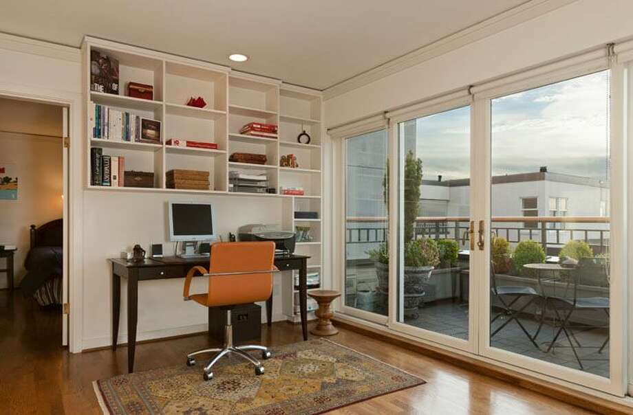 Office of 1009 Western Ave., No. 1209. The 2,024-square-foot home,  built in 1983, has two bedrooms, each with its own bathroom, a powder room, a den, 10-foot ceilings, two balconies and views of downtown, Elliot Bay and the Olympic Mountains. It's listed for $1.1 million. Photo: Courtesy Penny Lewis/Windermere Real Estate
