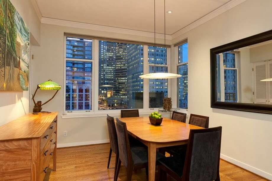 Dining room of 1009 Western Ave., No. 1209. The 2,024-square-foot home,  built in 1983, has two bedrooms, each with its own bathroom, a powder room, a den, 10-foot ceilings, two balconies and views of downtown, Elliot Bay and the Olympic Mountains. It's listed for $1.1 million. Photo: Courtesy Penny Lewis/Windermere Real Estate