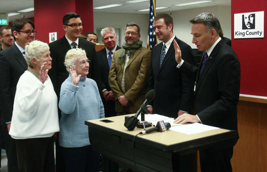 Jane Abbott Lightly and her partner Pete-e Petersen, right, take an oath that information provided is correct as King County Executive Dow Constantine presents them with a marriage license. Photo: JOSHUA TRUJILLO / SEATTLEPI.COM