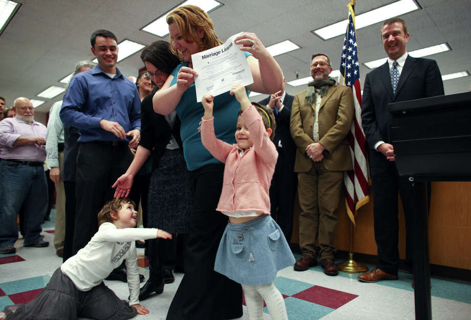 Parents Amanda Beane and Anne Bryson-Beane have help hoisting their marriage license as they are among the first to get the document. Photo: JOSHUA TRUJILLO / SEATTLEPI.COM