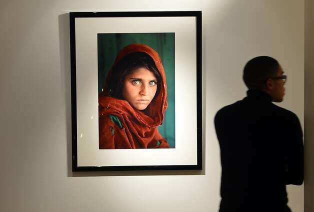 """Afghan Girl"" by photographer Steve McCurry, which graced the cover of National Geographic in 1985, sold for $147,000 to an anonymous bidder at an auction held in New York. Photo: Stan Honda, AFP/Getty Images"
