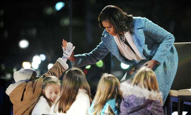 First lady Michelle Obama gives high five to kids after reading a story during the 90th National Christmas Tree Lighting Ceremony on the Ellipse behind the White House on December 6, 2012 in Washington, DC. This year is the 90th annual National Christmas Tree Lighting Ceremony. Photo: Pool, Getty Images / 2012 Getty Images