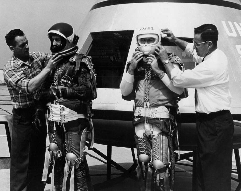 Three NASA personnel suited in space-flight restraining gear prepare to climb aboard the Apollo Spacecraft  April 6, 1962. This preliminary mock-up model was placed on display  April 6. 13ft. wide and 12ft. high, this command module will be the most complex manned flight device ever designed and built for earth orbit and lunar landing. (AP Photo) (AP)