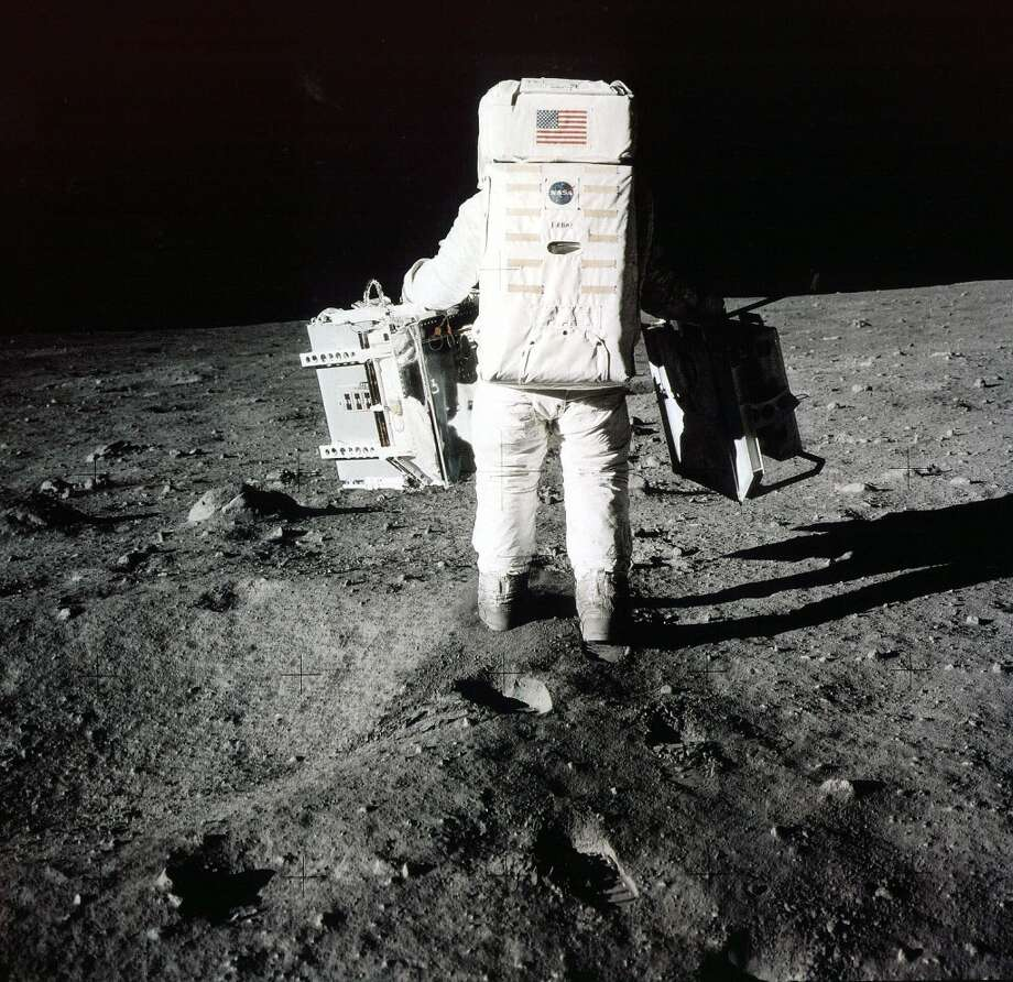 Edwin Buzz Aldrin carries scientific experiments to a deployment site south of the lunar module Eagle. One experiment involved the inner composition of the moon, and another tried to determine the exact distance from Earth. Photo was taken by Neil Armstrong of the Apollo 11 mission on July 20, 1969.  (AP Photo/NASA/Neil Armstrong) (AP)
