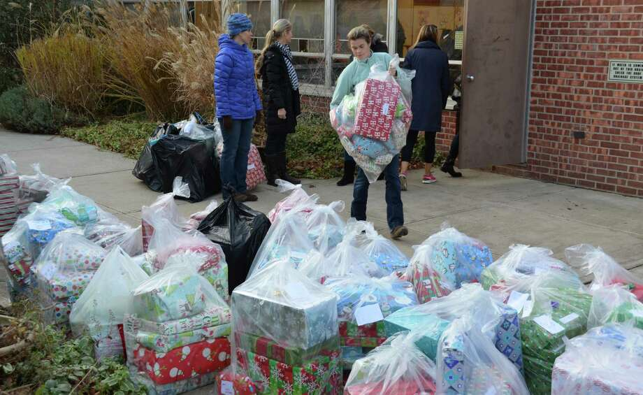 Bags of brightly wrapped holiday gifts line a walk at Long Lots School as even more are brought out of the biuilding to be shipped to two charitable organizations. Photo: Contributed Photo / Westport News contributed