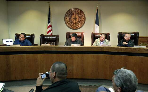 "Maverick County commissioners gather for a recent meeting in Eagle Pass with the chair of jailed Precinct 2 Commissioner Rodolfo ""Rudy"" Bainet Heredia sitting empty. Another county commissioner, Precinct 1's Commissioner Eliaz Maldonado (far right) turned himself in this past week to face bribery charges. Photo: Bob Owen, San Antonio Express-News / © 2012 San Antonio Express-News"