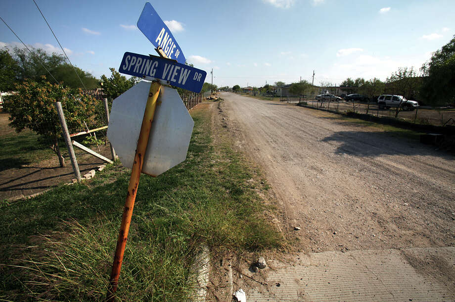 The intersection of Angie and Spring View drives in the Pueblo Nuevo colonia just outside of Eagle Pass may be made of concrete, but many of the streets in the area remain unpaved. Photo: Bob Owen, San Antonio Express-News / © 2012 San Antonio Express-News