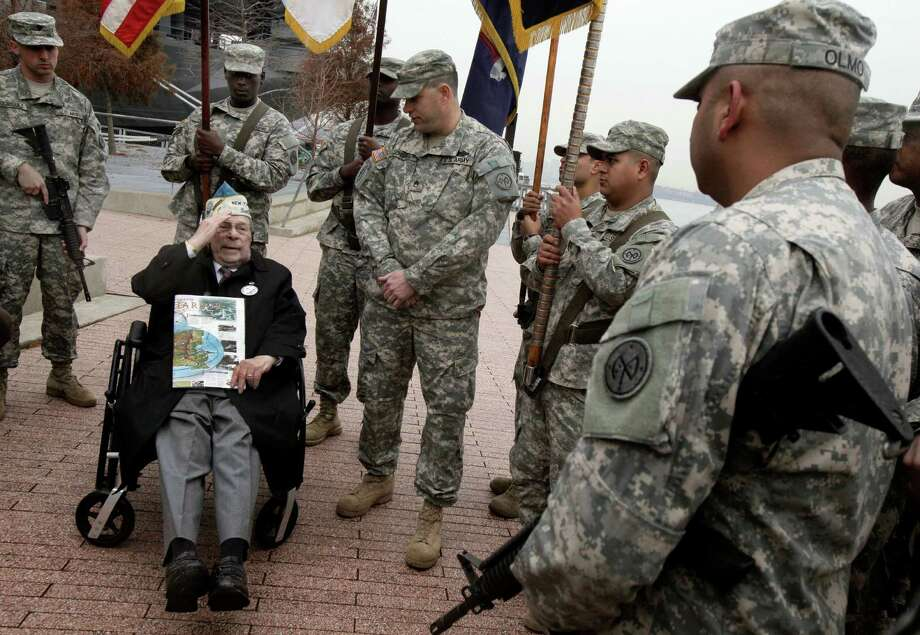 Pearl Harbor survivor Daniel Fruchter, of Eastchester, N.Y., salutes members of a color guard at the Intrepid Sea, Air and Space Museum in New York. Photo: Richard Drew, STF / AP