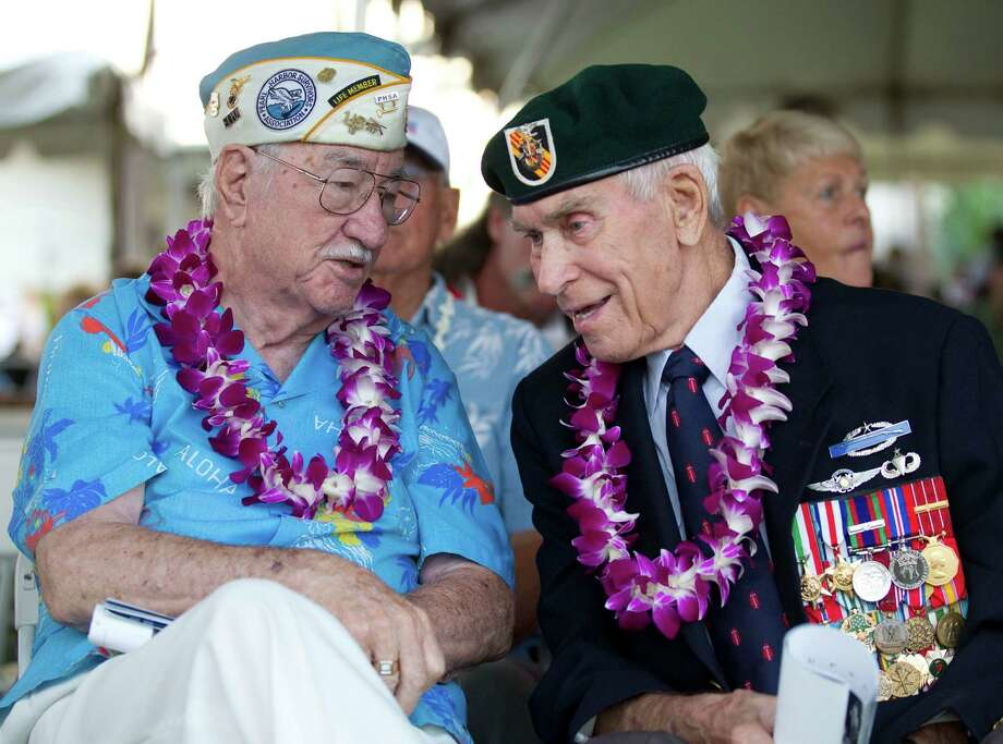 Pearl Harbor survivor Sam Clower, left, of Sacramento, Calif. and Ab Brum, right, , retired United States Army Special Forces, of Kaneohe, Hawaii, share memories of the Japanese attack on Pearl Harbor Friday, Dec. 7, 2012, at Pearl Harbor, Hawaii. Many of the Pearl Harbor Veterans gathered at the World War II Valor In The Pacific National Monument remembering the 71th anniversary of the Dec. 7, 1941 Japanese surprise attack on Pearl Harbor in Honolulu. (AP Photo/Eugene Tanner) Photo: Eugene Tanner, Associated Press / FR168001 AP
