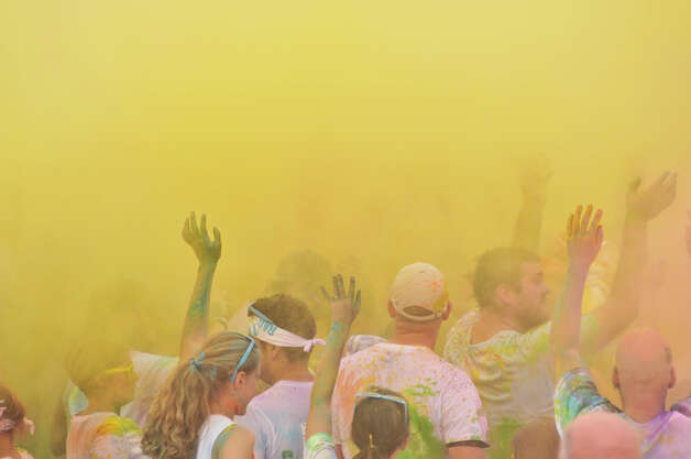 Runners stand in floating yellow powder  — nontoxic colored corn starch — during the Color Me Rad 5K Run.    