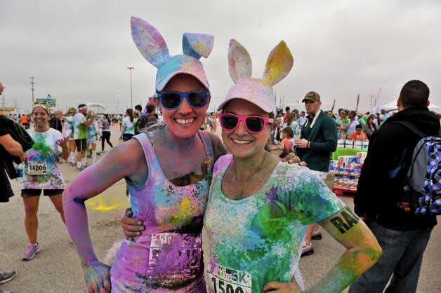 Covered in colored powder, Sarah Gaines (left) and Courtney Fultz are all ears at the event. Fun runs such as this one are are less about competition and more about having a good time. Photo: Robin Jerstad, For The Express-News