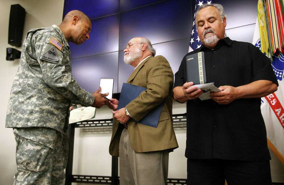 Dr. Jose Antonio Marquez, center, receives his father Pvt. Juan Candelaria Marquez's purple heart from Fort Bliss Commanding General, Maj. Gen. Dana J.H. Pittard as Dr. Ricardo Marquez, right, studies the Bronze star he just received for his father, Friday, Dec. 7, 2012 at Fort Bliss in El Paso, Texas.  Pvt. Juan Candelaria Marquez a World War II veteran injured in 1944 when he was struck by a German tank in France has been posthumously awarded a Purple Heart in a West Texas ceremony. (AP Photo/The El Paso Times, Mark Lambie)  EL DIARIO OUT; JUAREZ MEXICO OUT Photo: Mark Lambie, Associated Press / EL PASO TIMES
