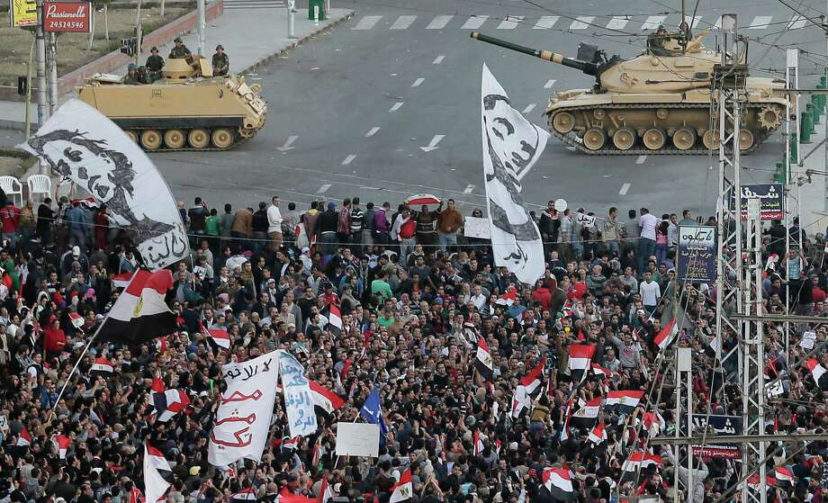 Egyptian army tanks, center, secure the perimeter of the presidential palace while protesters gather, chanting anti-president Mohammed Morsi slogans, in Cairo, Egypt, Friday. Photo: Hassan Ammar, STF / AP