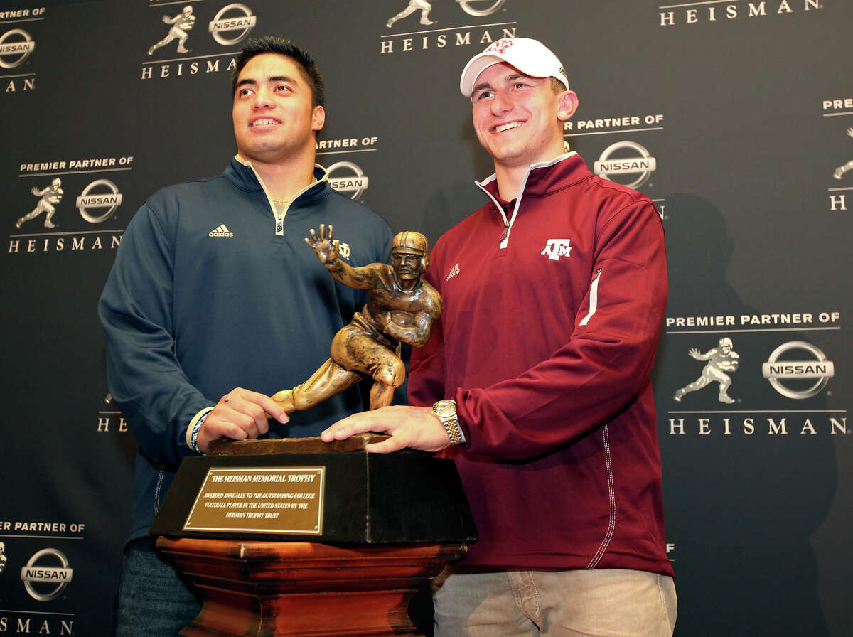 Heisman finalists Notre Dame's linebacker Manti Te'o and Texas A&M's quarterback Johnny Manziel pose with the Heisman Trophy during a press conference Friday Dec. 7, 2012 at the New York Marriott Marquis hotel in New York, New York. Not pictured is Heisman finalist Kansas State's quarterback Collin Klein.