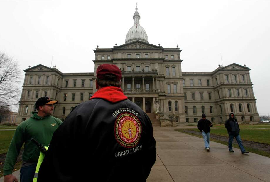 International Brotherhood of Electrical Workers members stand outside the capitol in Lansing, Friday, Dec. 7, 2012. Michigan could become the 24th state with a right-to-work law next week. Rules require a five-day wait before the House and Senate vote on each other's bills; lawmakers are scheduled to reconvene Tuesday and Gov.Snyder has pledged to sign the bills into law. (AP Photo/Paul Sancya) Photo: Paul Sancya, STF / AP