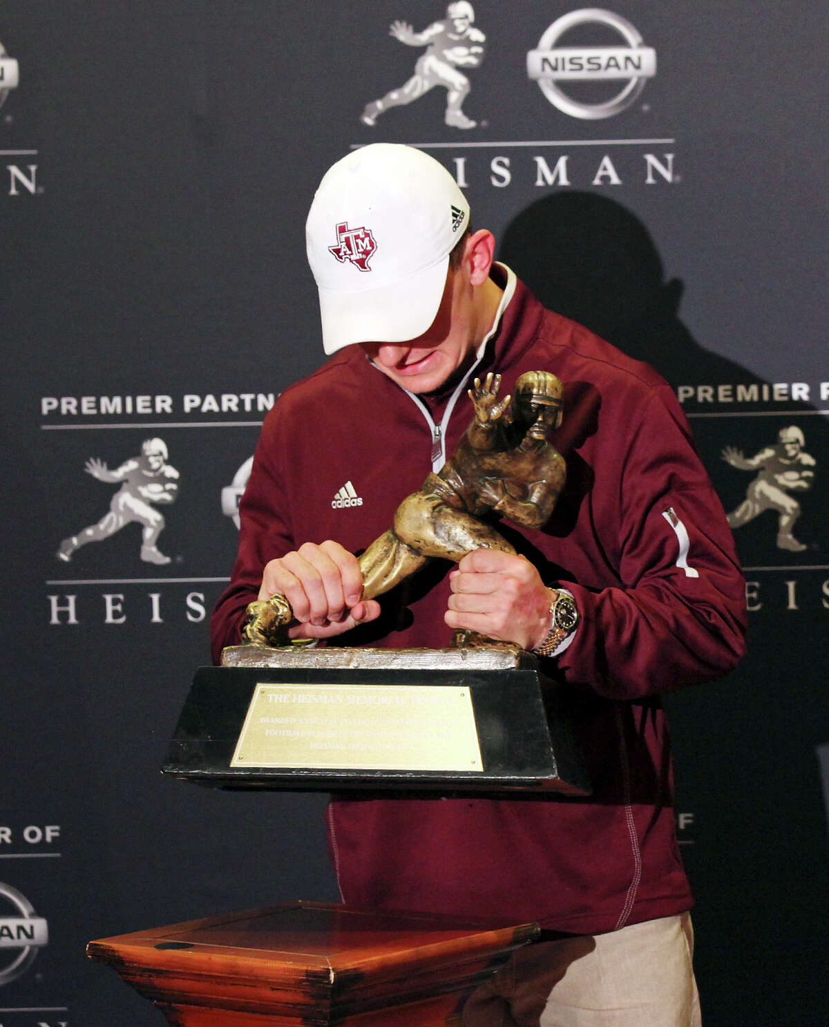 Heisman finalist Texas A&M's quarterback Johnny Manziel lifts the trophy as he poses for the media during a press conference Friday Dec. 7, 2012 at the New York Marriott Marquis hotel in New York, New York.