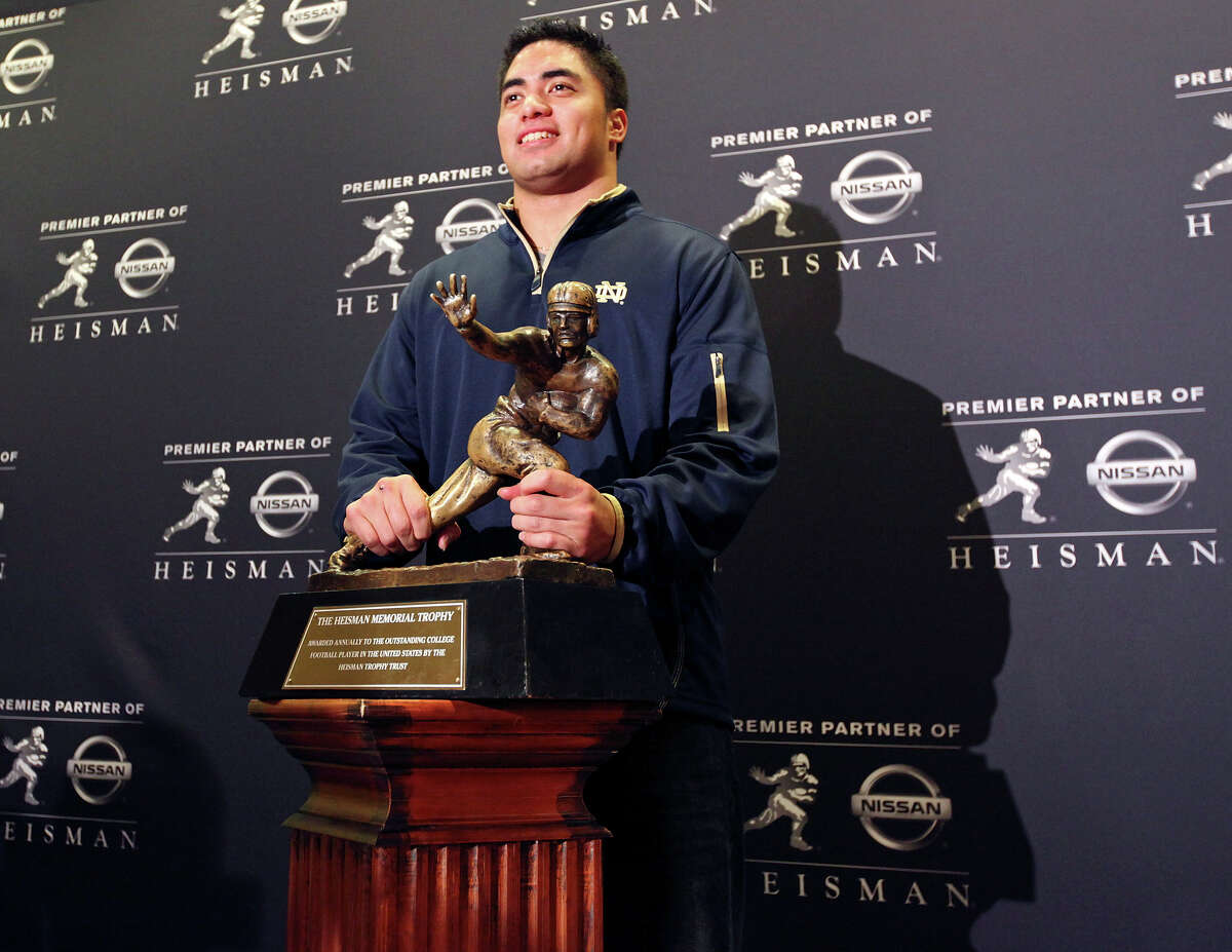 Heisman finalist Notre Dame's linebacker Manti Te'o poses with the Heisman Trophy during a press conference Friday Dec. 7, 2012 at the New York Marriott Marquis hotel in New York, New York.