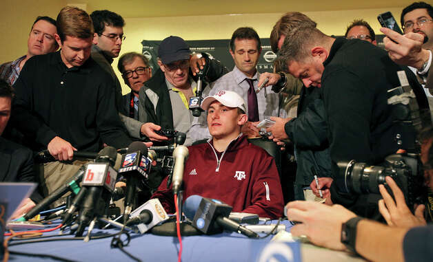 Heisman finalist Texas A&M's quarterback Johnny Manziel (center) answers questions from the media during a press conference Friday Dec. 7, 2012 at the New York Marriott Marquis hotel in New York, New York. Photo: Edward A. Ornelas, Express-News / © 2012 San Antonio Express-News