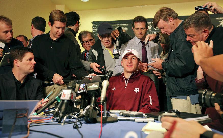 Heisman finalist Texas A&M's quarterback Johnny Manziel (center) answers questions from the media du
