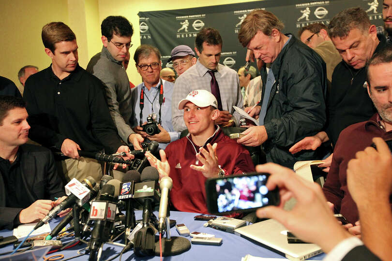 Heisman finalist Texas A&M's quarterback Johnny Manziel (center) answers questions from the media du