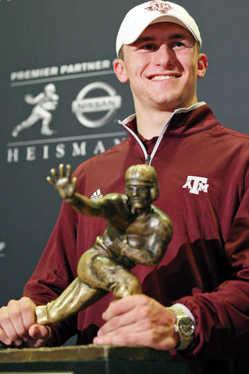 Heisman finalist Texas A&M's quarterback Johnny Manziel pose with the Heisman Trophy during a press