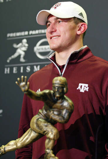 Heisman finalist Texas A&M's quarterback Johnny Manziel pose with the Heisman Trophy  during a press