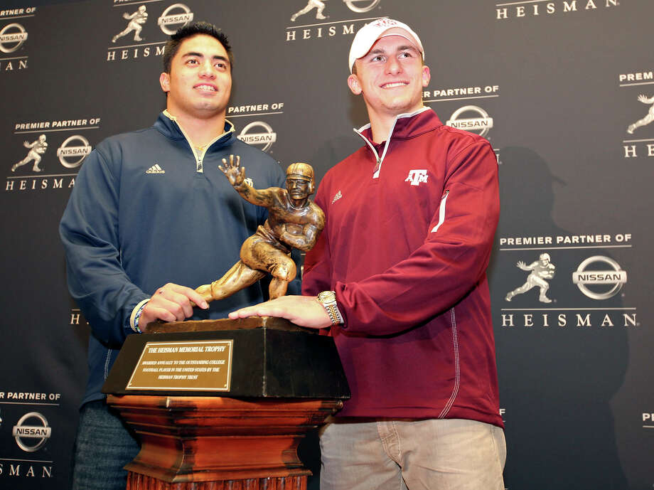 Heisman finalists Notre Dame's linebacker Manti Te'o (left) and Texas A&M's quarterback Johnny Manziel pose with the Heisman Trophy answer questions from the media during a press conference Friday Dec. 7, 2012 at the New York Marriott Marquis hotel in New York, New York. Not pictured is Heisman finalist Kansas State's quarterback Collin Klein. Photo: Edward A. Ornelas, Express-News / © 2012 San Antonio Express-News