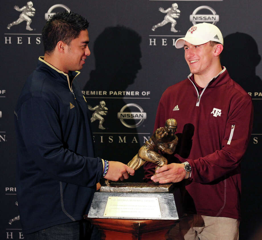 Heisman finalists Notre Dame's linebacker Manti Te'o (left) and Texas A&M's quarterback Johnny Manziel pose with the Heisman Trophy during a press conference Friday Dec. 7, 2012 at the New York Marriott Marquis hotel in New York, New York. Not pictured is Heisman finalist Kansas State's quarterback Collin Klein. Photo: Edward A. Ornelas, Express-News / © 2012 San Antonio Express-News