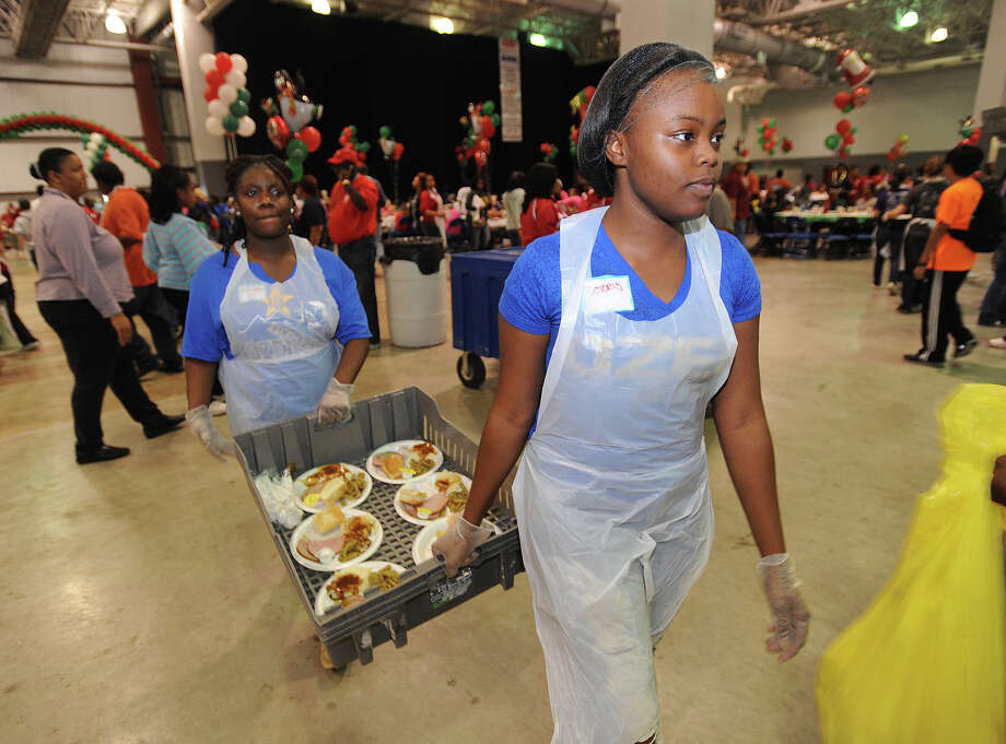 Deloris Bishop, right, and Mahogany Ellis carry plates of food to guests at the Feast of Sharing event at Ford Park on Friday. Sponsored by H-E-B, the event catered a free Christmas meal to thousands of people. Photo taken Friday, December 07, 2012 Guiseppe Barranco/The Enterprise Photo: Guiseppe Barranco, STAFF PHOTOGRAPHER / The Beaumont Enterprise