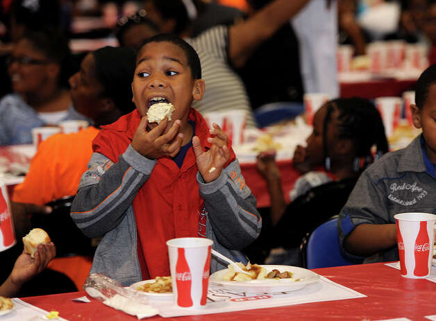 Larry Johnson, 8, takes a bite out of his Christmas dinner during the Feast of Sharing Event at Ford Park on Friday. Sponsored by H-E-B, the event catered a free Christmas meal to thousands of people. Photo taken Friday, December 07, 2012 Guiseppe Barranco/The Enterprise Photo: Guiseppe Barranco, STAFF PHOTOGRAPHER / The Beaumont Enterprise