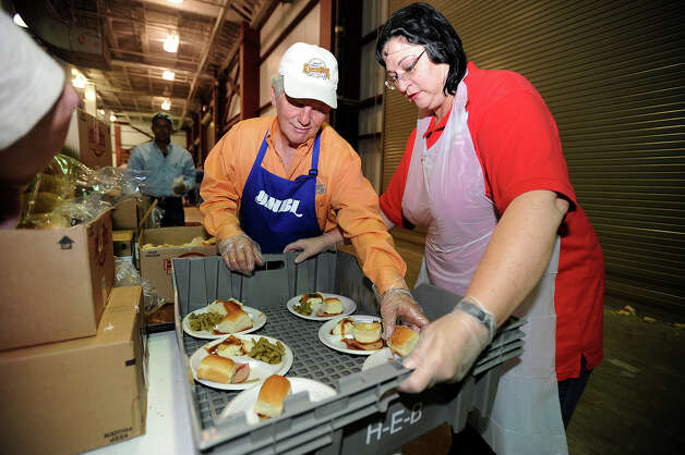 Deanna Martin and Woody Leone prepare plates of food for guests at the Feast of Sharing event at Ford Park on Friday. Sponsored by H-E-B, the event catered a free Christmas meal to thousands of people. Photo taken Friday, December 07, 2012 Guiseppe Barranco/The Enterprise Photo: Guiseppe Barranco, STAFF PHOTOGRAPHER / The Beaumont Enterprise