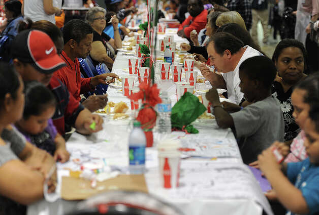 Guests were served Christmas dinners by several volunteers during the H-E-B Sponsored Feast of Sharing  event catered a free Christmas meal to thousands of people. Photo taken Friday, December 07, 2012 Guiseppe Barranco/The Enterprise Photo: Guiseppe Barranco, STAFF PHOTOGRAPHER / The Beaumont Enterprise