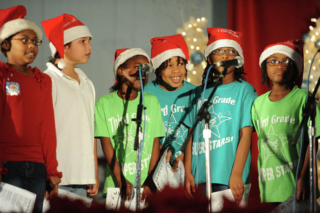 Pietzsch-MacArthur Elementary School's third grade choir students sing Christmas carols to guests at the Feast of Sharing event at Ford Park on Friday. Sponsored by H-E-B, the event catered a free Christmas meal to thousands of people. Photo taken Friday, December 07, 2012 Guiseppe Barranco/The Enterprise Photo: Guiseppe Barranco, STAFF PHOTOGRAPHER / The Beaumont Enterprise