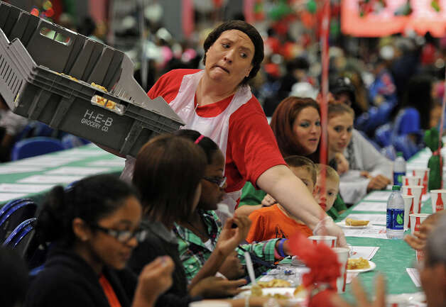 Tonya Piper stretches to hand guests pies during the Feast of Sharing event at Ford Park on Friday. Sponsored by H-E-B, the event catered a free Christmas meal to thousands of people. Photo taken Friday, December 07, 2012 Guiseppe Barranco/The Enterprise Photo: Guiseppe Barranco, STAFF PHOTOGRAPHER / The Beaumont Enterprise