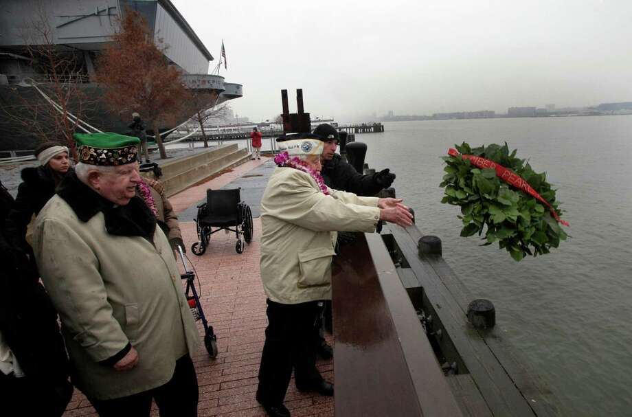 Pearl Harbor survivor Armando Chick Galella, right, age 91, of Sleepy Hollow, N.Y., tosses a wreath into the Hudson River during ceremonies at the Intrepid Sea, Air and Space Museum. in New York, commemorating the 71st anniversary of the attack at Pearl Harbor, Friday, Dec. 7, 2012. President Barack Obama marked the day on Thursday by issuing a presidential proclamation, calling for flags to fly at half-staff on Friday and asking all Americans to observe the day of remembrance and honor military service members and veterans. Photo: Richard Drew, Associated Press / AP