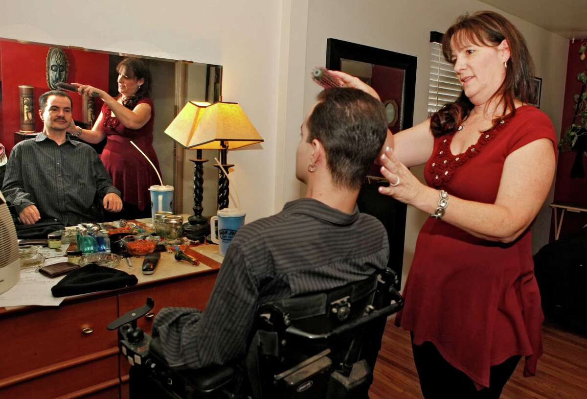 Brandon Coats' mother Donna brushes Brandon's hair at his home in Denver on Thursday. Paralyzed as a teenager in a car crash, he's been a medical marijuana patient since 2009. Coats, 33, was fired in 2010 for failing a company drug test.