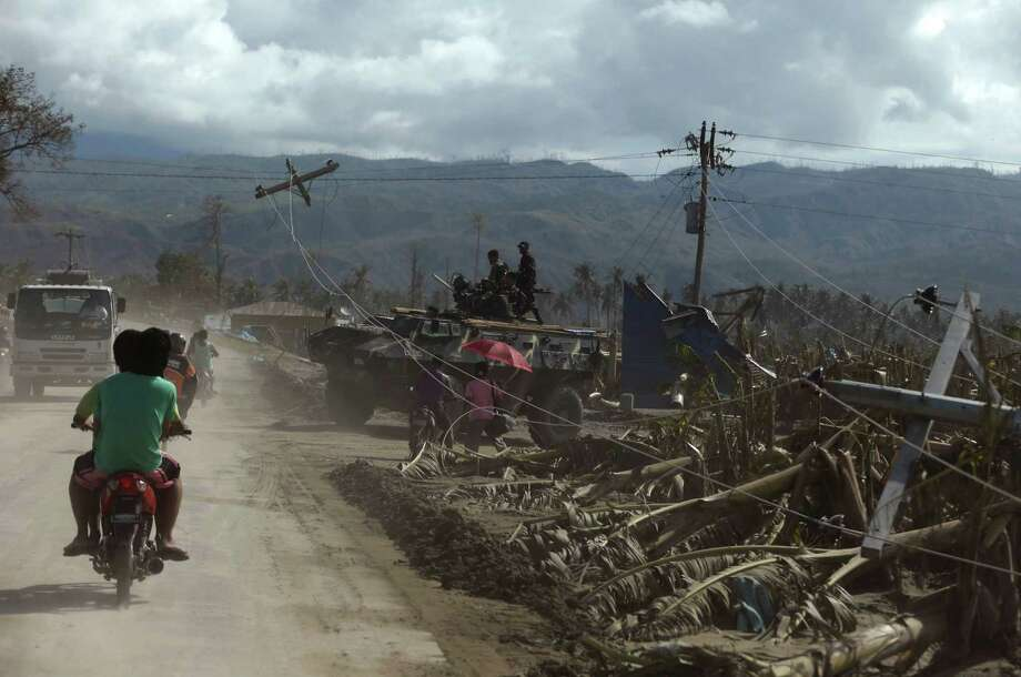 "Commuters pass by a banana plantation that was destroyed at the height of Tuesday's typhoon named ""Bopha"" at Nabunturan township, Compostela Valley in southern Philippines Friday Dec. 7, 2012. The economic losses began to emerge Friday after export banana growers reported that 14,000 hectares (34,600 acres) of export banana plantations, equal to 18 percent of the total in Mindanao, were destroyed. The Philippines is the world's third-largest banana producer and exporter, supplying well-known brands such as Dole, Chiquita and Del Monte mainly to Japan and also to South Korea, China, New Zealand and the Middle East. Photo: Bullit Marquez, Associated Press / AP"