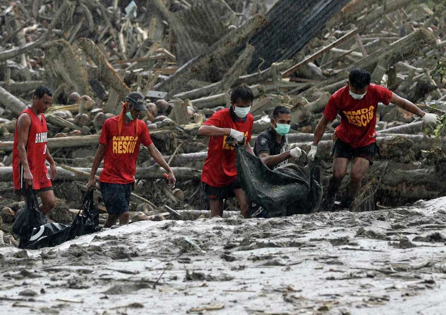 Rescuers retrieve flash flood victims from the debris of Tuesday's Typhoon Bopha at New Bataan township, Compostela Valley in southern Philippines Friday Dec. 7, 2012. Rescuers were digging through mud and debris Friday to retrieve more bodies strewn across a farming valley in the southern Philippines by a powerful typhoon. Photo: Bullit Marquez, Associated Press / AP
