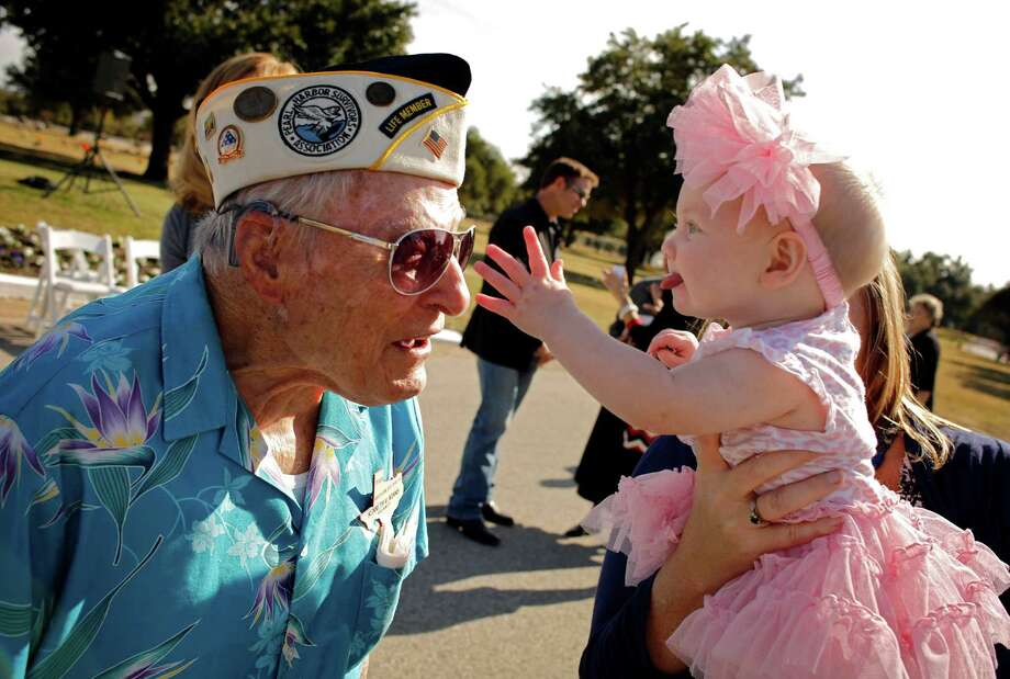 Pearl Harbor survivor Kenneth Adams, left, leans out as 6-month-old Kalani Parsons, the great-granddaughter of fellow survivor Charles Peters, reaches to touch his medals during the Pearl Harbor 71st Anniversary Memorial Service Friday, Dec. 7, 2012 at Laurel Land Memorial Park in Dallas. Photo: G.J. McCarthy, Associated Press / The Dallas Morning News
