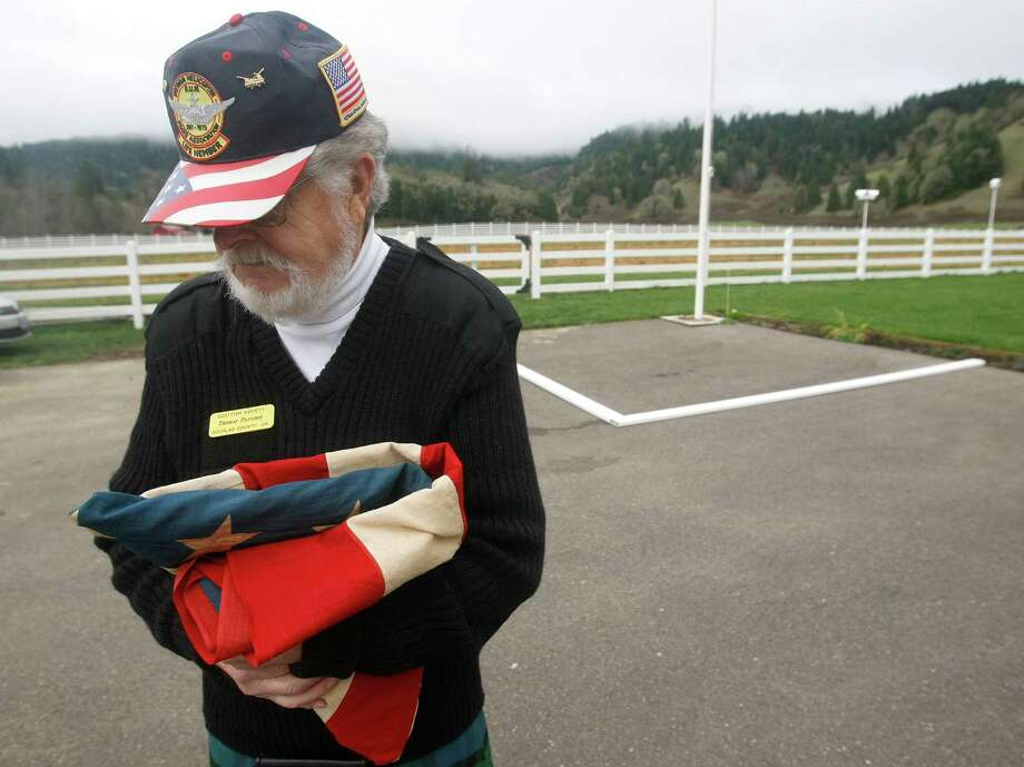 Tom Paulson of Lookingglass, Ore. holds a 48 star U.S. flag before it is raised at the  home of Del Blanchard in recognition of Pearl Harbor Day Friday, Dec. 7, 2012, in Myrtle Creek, Ore. Photo: Michael Sullivan, Associated Press / The News-Review