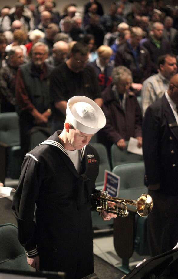 "Navy Band Northwest trumpet player Petty Officer 1st class Justin Strauss bows during the invocation at the Pearl Harbor Remembrance, Friday, Dec. 7, 2012, at Naval Undersea Museum in Keyport, Wash. He also played "" Taps"" at the event. Photo: Larry Steagall, Associated Press / Kitsap Sun"