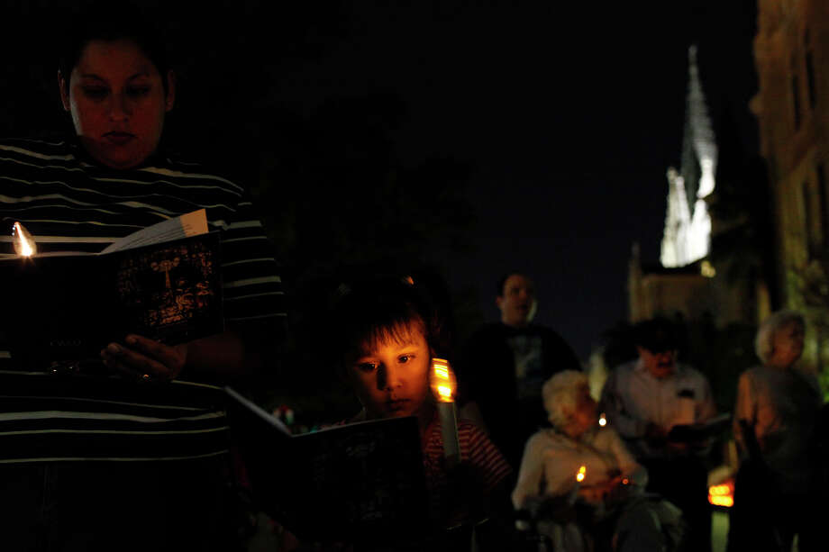 Kaylee Kanevsky, 5, stands with her mother, Cindy Kanevsky, left, during Las Posadas at Our Lady of the Lake University on Friday, Dec. 7, 2012. Kaylee's other mother, Maria Navarro, is a student at the university. Photo: Lisa Krantz, San Antonio Express-News / © 2012 San Antonio Express-News