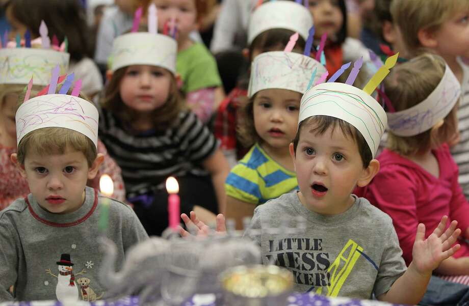 "Two-year-olds Thomas Ford, left, and Ian Hoffman, right, sing as they celebrate Hanukah, the Festival of Lights, at Bertha Alyce Early Childhood Center at the Evelyn Rubenstein Jewish Community Center of Houston, Friday, Dec. 7, 2012, in Houston. The children sang and took part in a play that told the story of how Chanukah began. The story is the triumph of the Jewish Maccabees against the Assyrian Army and King Antiochus.  The lighting of the Chanukah menorah, ""Chanukiah"" for eight days commemorates the miracle of the temple menorah's oil burning for eight days on one days worth of olive oil. Photo: Karen Warren, Houston Chronicle / © 2012  Houston Chronicle"