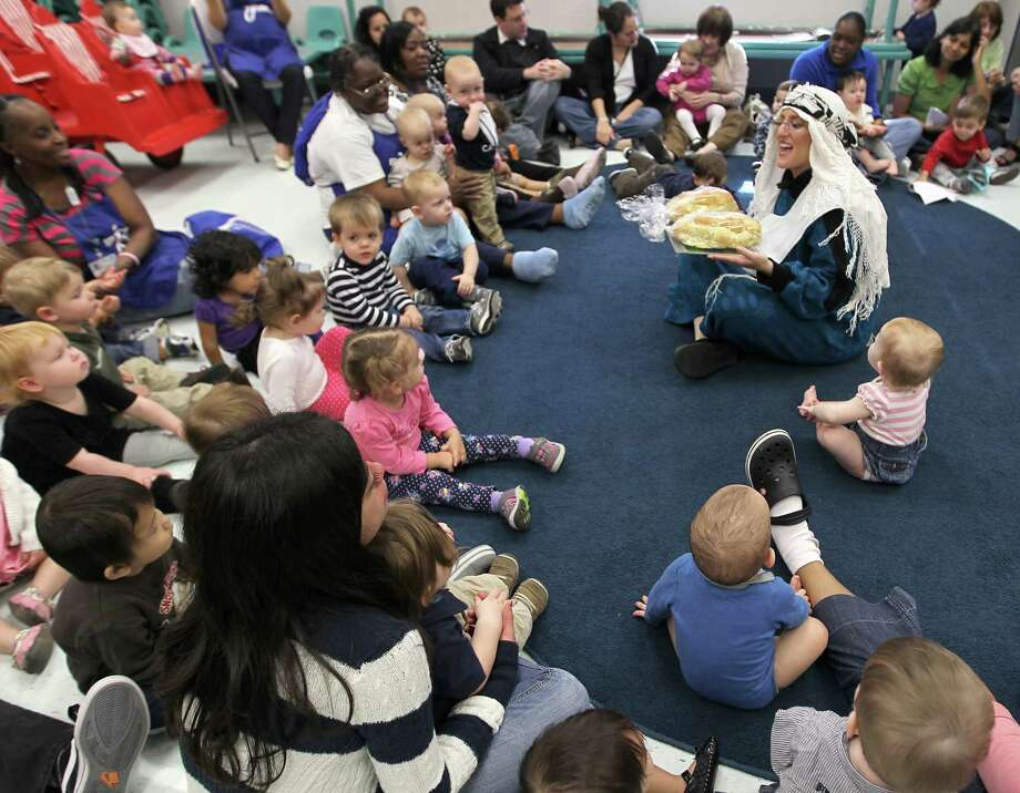 Alana Shepetofsky, Judaic Curriculum Specialist, holds Challah bread as she teaches a group of babies and toddlers during a celebration of Hanukah, the Festival of Lights, at Bertha Alyce Early Childhood Center at the Evelyn Rubenstein Jewish Community Center of Houston, Friday, Dec. 7, 2012, in Houston. Photo: Karen Warren, Houston Chronicle / © 2012  Houston Chronicle