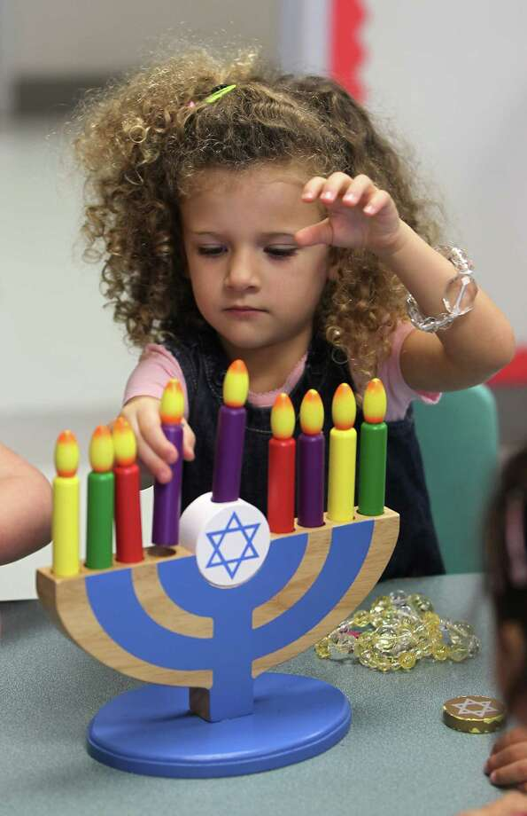 Avery Fisher plays with a toy menorah during the three-year-old pre-school class as they celebrate Hanukah, the Festival of Lights, at Bertha Alyce Early Childhood Center at the Evelyn Rubenstein Jewish Community Center of Houston, Friday, Dec. 7, 2012, in Houston. Photo: Karen Warren, Houston Chronicle / © 2012  Houston Chronicle